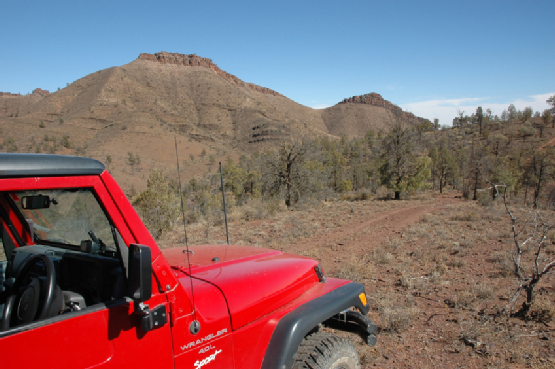 Red Jeep Wrangler driving offroad rocky track in Flinders Ranges